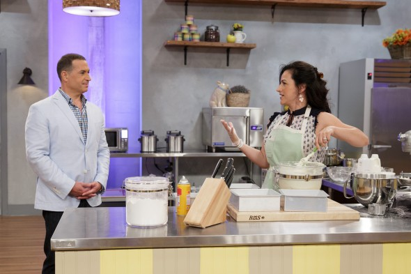 "Contestant Audrey McGinnis, right, talks to host Bobby Deen, left, as she mixes batter for a white chocolate cake during the ""Berry Naked Cake"" main-heat challenge, as seen on Food Network's Spring Baking Championship, Season 2."
